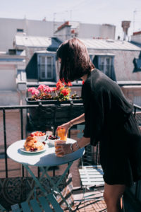 Donna che apparecchia tavolo per colazione sul terrazzo con abito nero