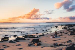 Donna seduta sulla spiaggia in riva al mare che guarda l'orizzonte