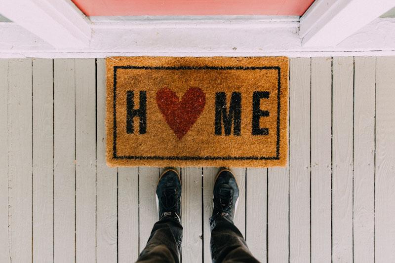 Piedi davanti a zerbino fuori ingresso casa con scritta home